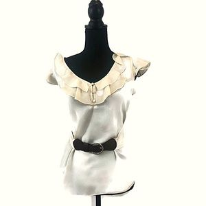 White ruffled blouse with matching belt.
